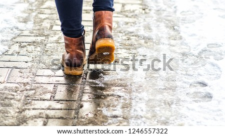 Walk on wet melted ice pavement. Back view on the feet of a man walking along the icy pavement. Pair of shoe on icy road in winter. Abstract empty blank winter weather background Royalty-Free Stock Photo #1246557322
