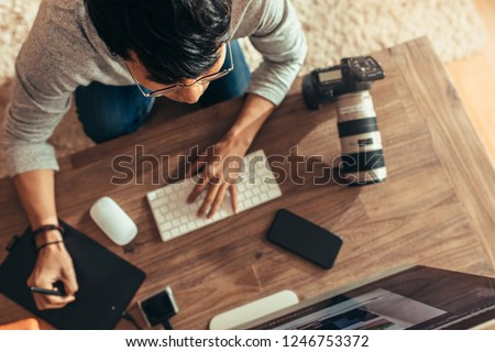 Overhead view of photographer editing photos at his studio. Photographer editing photos after a photo shoot using graphic tablet and stylus pen. Focus on photographer.