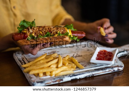 Woman is holding hot dog fully loaded with assorted toppings. Young girl is eating fast food. American meal with french fries on rustic wooden board. Selective focus. Toned image. #1246857379