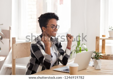 Excited African American woman in glasses read good news online at laptop, happy black female get promotional letter or email celebrating goal achievement, smiling girl look at computer lucky with win #1246919782
