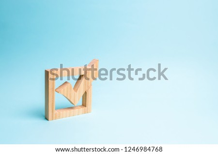 wooden checkmark for voting on elections on a blue background. Presidency or parliamentary elections, a referendum. Survey of the population, statistics, completed task. Democracy and freedom #1246984768
