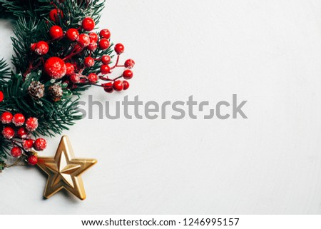 Christmas decorative wreath of holly, ivy, mistletoe, cedar and leyland leaf sprigs with red berries over white background #1246995157