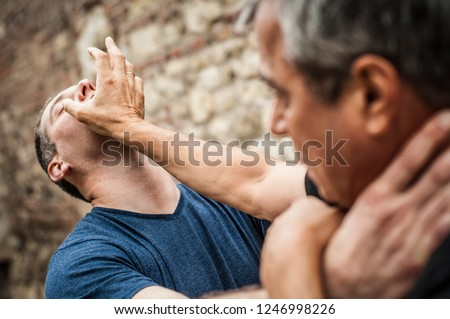 Kapap instructor demonstrates street fighting self defence technique against holds and grabs with his student. Martial arts #1246998226