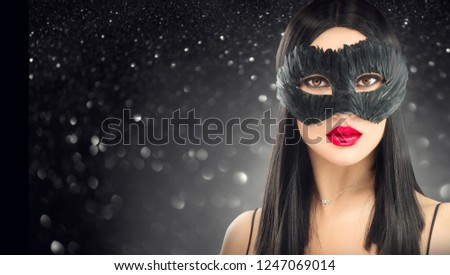 Beauty Glamour brunette Woman celebrating, wearing carnival feather dark mask, party over holiday glowing black background. Christmas and New Year Holiday celebration, Holiday make-up, red lips #1247069014