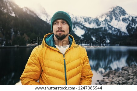 Young bearded man wearing yellow puff jacket and green hat standing near a mountain lake in winter. Snow mountain on background.   #1247085544