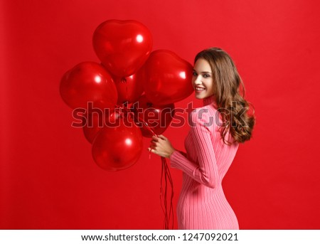 young beautiful emotional girl in pink dress with red ballons on red background