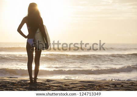 Rear view of beautiful sexy young woman surfer girl in bikini with white surfboard on a beach at sunset or sunrise #124713349