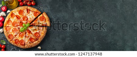 Tasty pepperoni pizza and cooking ingredients tomatoes basil on black concrete background. Top view of hot pepperoni pizza. With copy space for text. Flat lay. Banner #1247137948