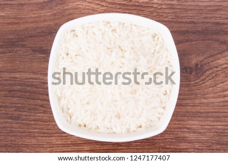 Heap of white rice in glass bowl on board, concept of healthy nutrition #1247177407