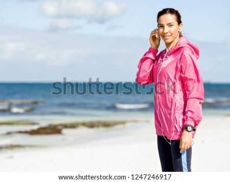 Sporty woman with earphones on the sea coast #1247246917