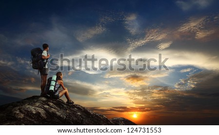 Two tourists with backpacks relaxing on top of a mountain and enjoying sunset view #124731553