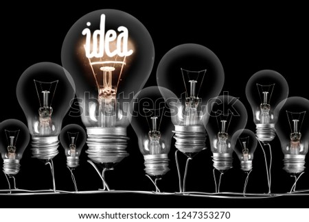 Photo of dark and shining light bulbs with fibe in IDEA shape; concept of idea, innovation, uniqueness and standing out; isolated on black background #1247353270