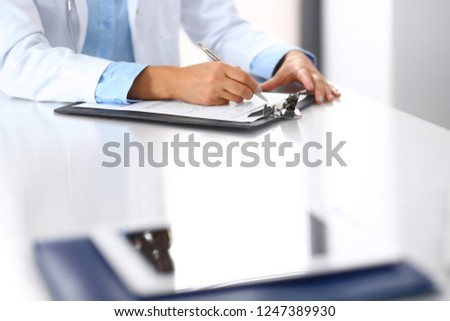 Unknown doctor woman filling up medical form while sitting at the desk in hospital office, close-up of hands. Physician at work. Medicine and health care concept #1247389930