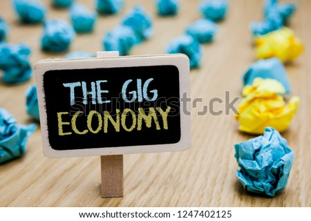 Conceptual hand writing showing The Gig Economy. Business photo text Market of Short-term contracts freelance work temporary poster board with blurry paper lobs laid serially mid yellow lob. #1247402125