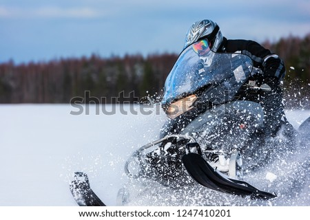 In deep snowdrift snowmobile rider driving fast. Riding with fun in white snow powder during backcountry tour. Extreme sport adventure, outdoor activity during winter holiday on ski mountain resort. #1247410201