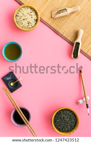 Chinese traditional symbols concept. Tea, rice, hieroglyph love, bamboo table mat, chopsticks, soy sause on pink background top view frame copy space #1247423512