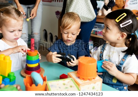 Nursery children playing with teacher in the classroom Royalty-Free Stock Photo #1247434123