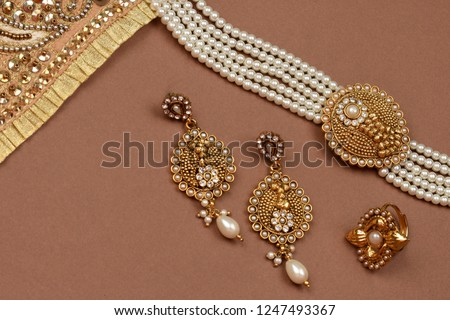 Pearl Jewelry on a brown background,Golden scarf,Pearl bracelet,pearl hair clip,pearl necklace pearl earrings,finger ring.fashion and design of jewelry. Indian traditional jewellery,jewelry background #1247493367