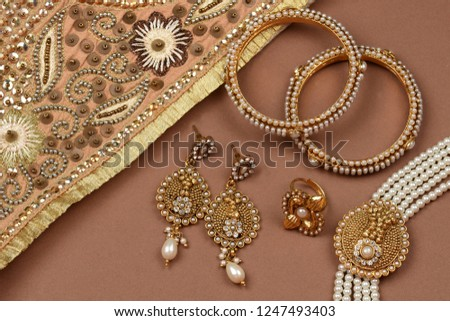Pearl Jewelry on a brown background,Golden scarf,Pearl bracelet,pearl hair clip,pearl necklace pearl earrings,finger ring.fashion and design of jewelry. Indian traditional jewellery,jewelry background #1247493403