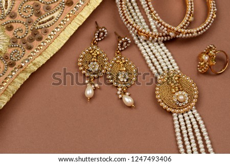 Pearl Jewelry on a brown background,Golden scarf,Pearl bracelet,pearl hair clip,pearl necklace pearl earrings,finger ring.fashion and design of jewelry. Indian traditional jewellery,jewelry background #1247493406