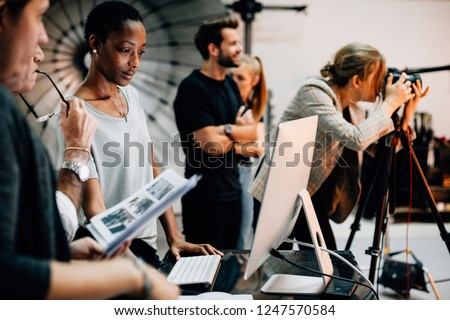 Art director checking the photos on a monitor Royalty-Free Stock Photo #1247570584