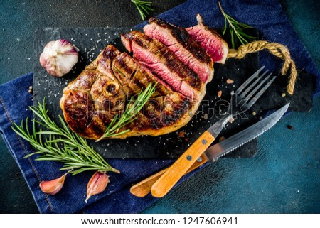 Sliced grilled roast beef with fork for meat and wine on wooden cutting board. Dark blue background. Top view copy space #1247606941