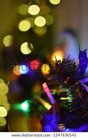 Closeup of coloured lights with bokeh lights in the background. Festive lights wrapped around a wreath. #1247630545