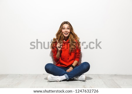 Full length photo of attractive woman 20s wearing casual clothes smiling while sitting on floor with legs crossed isolated over white background