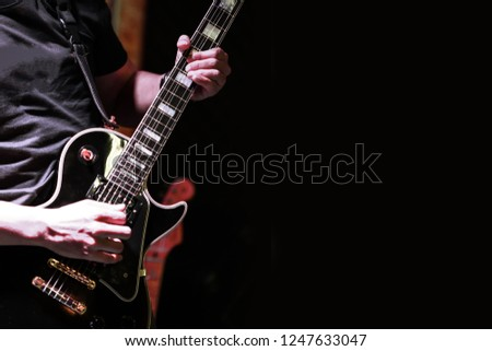 Guitarist on stage for background, soft and blur concept. Close up hand playing guitar. young musician playing guitar, live music background.Band performs on stage, rock music concert. #1247633047