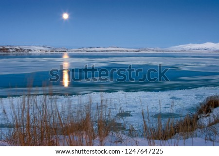 November. Ice drift in the Anadyr estuary. Twilight. Visible moon and moonlight on the water. Anadyr, Chukotka, Russia. #1247647225