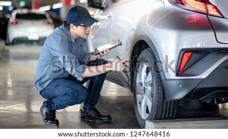 Young Asian auto mechanic holding digital tablet checking car wheel in auto service garage. Mechanical maintenance engineer working in automotive industry. Automobile servicing and repair concept #1247648416