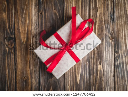 gift with red ribbon on the wooden table #1247706412