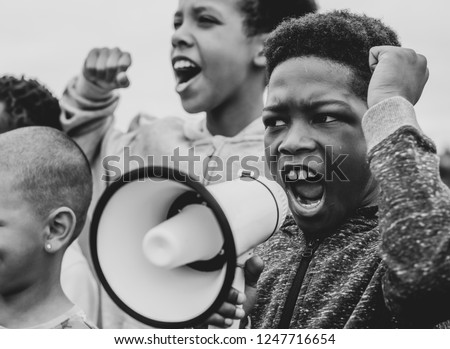 Young boy shouting on a megaphone in a protest Royalty-Free Stock Photo #1247716654