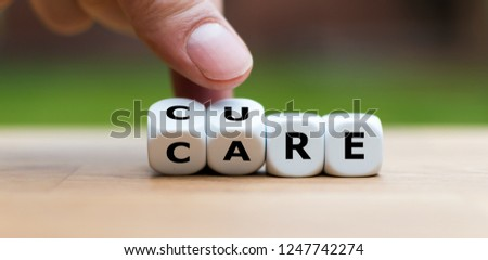 """Hand is turning dices and changes the word """"CARE"""" to """"CURE"""" Royalty-Free Stock Photo #1247742274"""