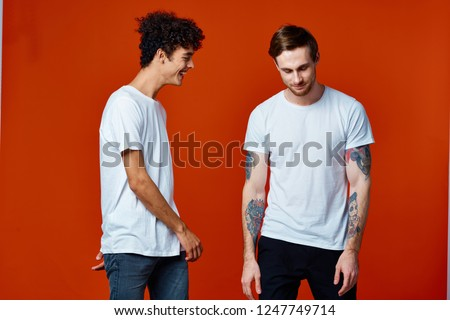 Two men in white t-shirts on a red background                   #1247749714
