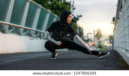Hijab girl exercising on walkway bridge in early morning. Muslim woman wearing sports clothes doing stretching workout outdoors. Royalty-Free Stock Photo #1247806204