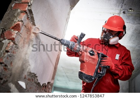 Demolition and construction destroying. worker with hammer breaking interior wall plastering #1247853847