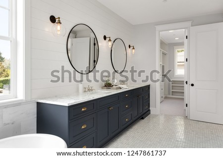 Beautiful White and Bright Bathroom in New Luxury Home with Large Vanity and Dark Blue Cabinets.Features Bathtub and Two Sinks, and Circular Mirrors. Shows Walk-In Closet   #1247861737