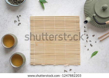 Asian Tea Set -  iron teapot and ceramic teacups with green tea. Traditional tea composition on white background with bamboo mat, copy space. #1247882203