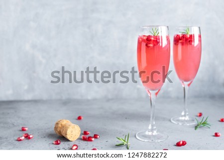Pomegranate Champagne Mimosa Cocktail (Mocktail) with rosemary on concrete background, copy space. Mimosa Drink for Valentine Day or other holidays. #1247882272