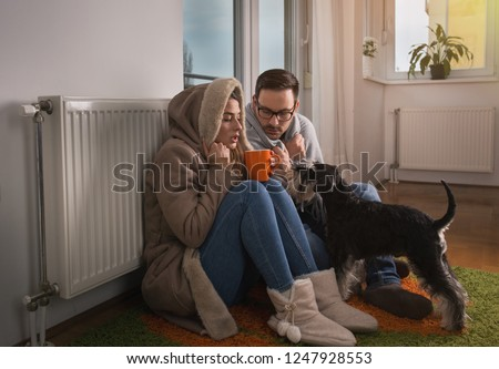 Young couple in jacket and covered with blanket sitting on floor beside radiator with dog and trying to warm up #1247928553