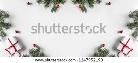 Creative frame made of Christmas fir branches on white paper background with red decoration, pine cones. Xmas and New Year theme. Flat lay, top view #1247952190