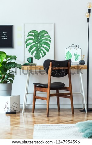 Stylish scandinavian open space with  office desk with mock up poster frames, a lot of plants and office accessories. Brown wooden parquet and white backgrounds wall. Floral concept of interior decor. #1247954596