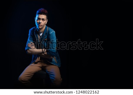 Woman musician with red hair in a denim suit posing on a black background #1248022162