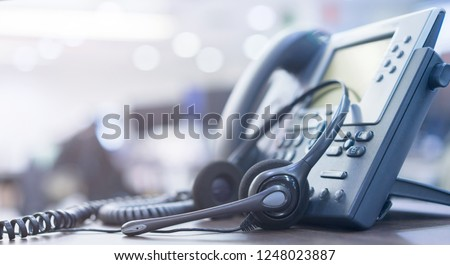 close up soft focus on telephone devices with copy space background at office desk in operation room for customer service support (call center) concept #1248023887