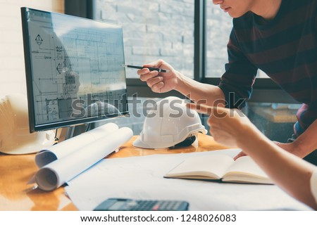Image of engineer or architect partner meeting for working with architectural project, drawing and sketching for inspection architectural project on blueprint at workspace. Royalty-Free Stock Photo #1248026083