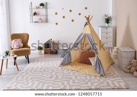 Cozy kids room interior with play tent and toys #1248057715