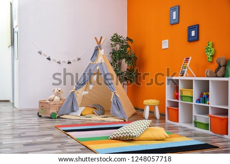 Cozy kids room interior with play tent and toys #1248057718