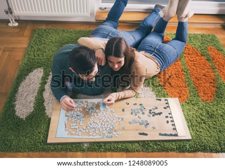 Top view of young couple laying on floor and doing puzzle Royalty-Free Stock Photo #1248089005
