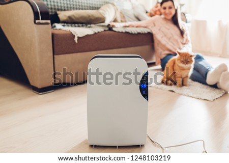 Dehumidifier with touch panel, humidity indicator, uv lamp, air ionizer, water container works at home while people chilling. Dampness concept #1248103219
